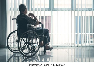 Back view of elderly man looks pensive while sitting in the wheelchair by the window. Shot in the retirement home