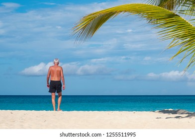 Back View of an Elderly Man Walking on a Caribbean Beach Towards the Ocean