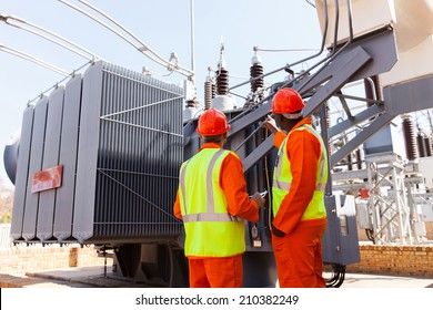 back view of electricians standing next to a transformer in electrical power plant