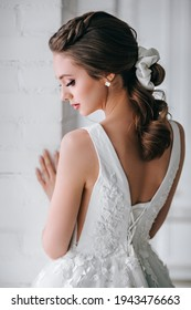 Back view of the elegant blonde bride dressed in a white dress in studio