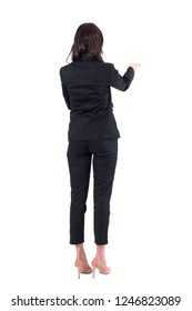 Back view of elegant business woman in black suit pointing at copyspace during presentation. Full body isolated on white background.