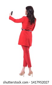 Back view of elegant business woman in red suit taking selfie photos with smart phone. Full body isolated on white background.