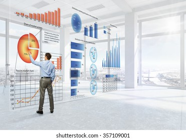 Back view of elegant businessman against modern ofiice window drawing infographs