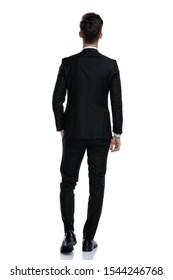 back view of elegant man in tuxedo walking isolated on white background, full body