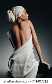 back view of elegant sensual african american woman posing in white cloth and turban, on grey