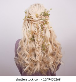 Back view of an elegant trendy hairstyle, interlacing curls and decorating with flower petals. Beautiful and well-groomed blonde hair