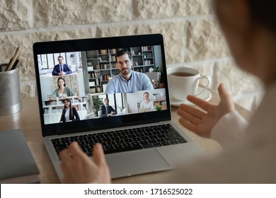 Back view of employee have webcam online conference or conversation with diverse colleagues coworkers, businesspeople talk on video call on laptop, brainstorm discuss business ideas on internet