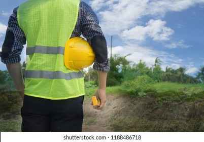 Back view of engineer, architect, supervisor worker, wearing green reflective vest, holding yellow safety helmet, water level gauge at construction site, empty land. Real estate, Home building concept