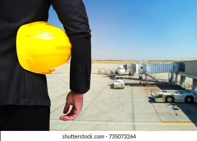 back view of engineer and holding yellow safety helmet standing in front of loading cargo on the plane at airport background, industrial, logistics, transportation and business concept