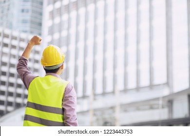 back view of engineering man construction worker wear safety helmet and wear reflective clothing for the safety of the work operation. engineer standing raised arms fist cheerful show project success