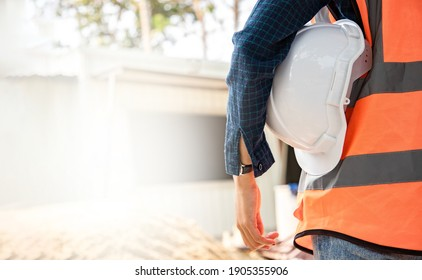 Back view of environmental engineering standing and holding hardhat at the work site. Background of modern office buildings with park