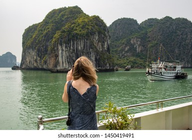 Back view of European tourist travel in Halong Bay the UNESCO world heritage site in Vietnam. The bay features thousands of limestone Karst in various shapes and sizes.