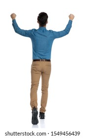 back view of excited young man in blue shirt celebrating victory and walking with arms in the air, isolated on white background, full body