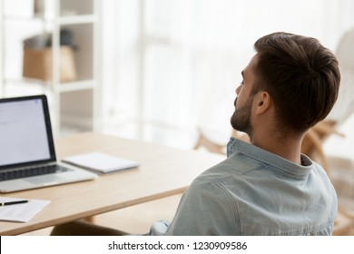 Back view of exhausted millennial man sit at workplace falling asleep, tired male worker distracted from work taking break or nap near laptop, sleepy guy relax with eyes closed sleeping near computer