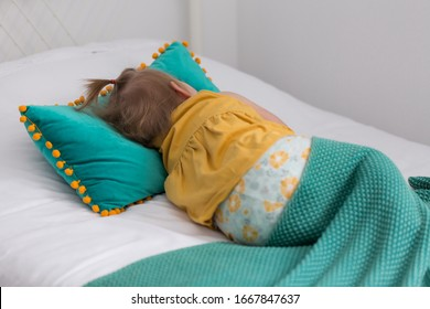 Back view of fair toddler girl in yellow top lying down in bed relaxing under turquoise throw blanket