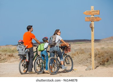 Back view of family with baby and girl child having a weekend excursion on their bikes on a summer day in beautiful landscape