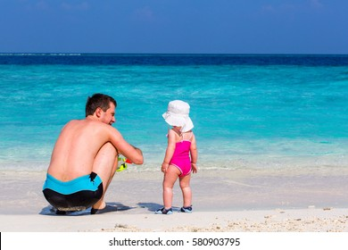 Back view family dad and little daughter in a pink bathing suit and hat playing on white beach enjoying tropical summer vacation.