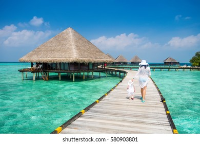 Back view family mother and daughter in white dress walking on wooden deck near the beach enjoying tropical summer vacation. Background water bungalow and the beauty of the sea with the coral reefs