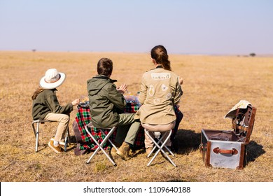 Back view family of mother and kids on African safari vacation enjoying bush breakfast