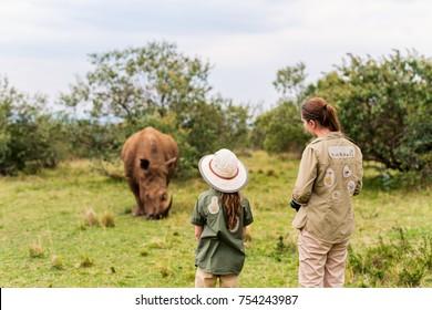 Back view of family on safari walking close to  white rhino