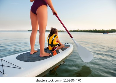 Back view of a family paddling on sup board