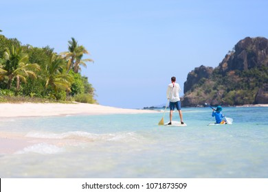 back view of family of two, father and son, enjoying stand up paddleboarding together in beautiful lagoon, active tropical vacation concept