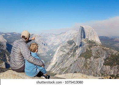 back view of family of two, father and son, sitting together at glacier point and enjoying view of half dome and yosemite valley in yosemite national park, california, adventure vacation concept