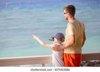 back view of family of two, father and son, using binoculars and looking ahead and pointing at something with finger, vacation concept