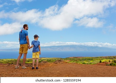 back view of family of two, father and son, at lanai island in hawaii enjoying view of keahiakawelo, garden of gods, and molokai island, copy space on right, summer family adventure vacation concept