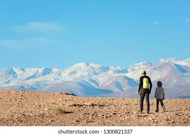back view of family of two, father and son, hiking and walking together enjoying valle de la muerte in atacama desert, chile, healthy active family lifestyle and vacation concept