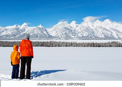 back view of family of two, father and son, enjoying gorgeous view of teton range in grand teton national park, wyoming, usa at winter