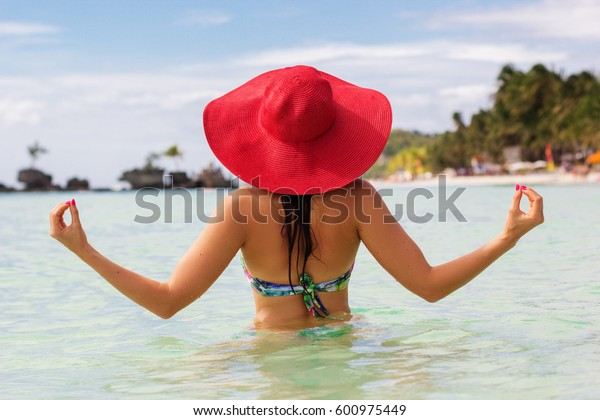 Back view of fashion woman is doing meditation on the beach and wearing red hat, summer vacations