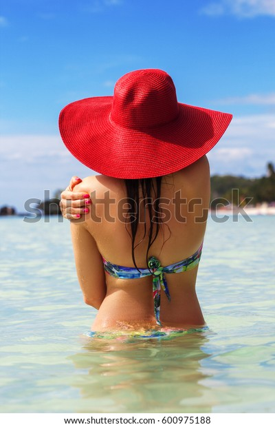 Back view of fashion woman is swimming on the beach and wearing red hat, summer vacations