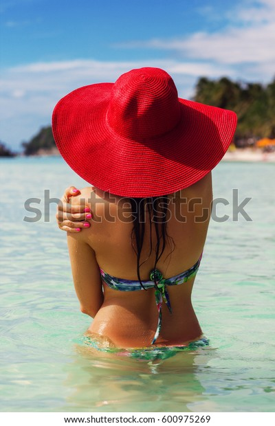 Back view of fashion woman is swimming on the beach and wearing red hat, summer vacations in Philippines