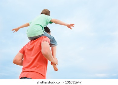 Back view of father carrying his son on shoulders