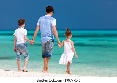 Back view of father and kids at tropical beach during summer vacation
