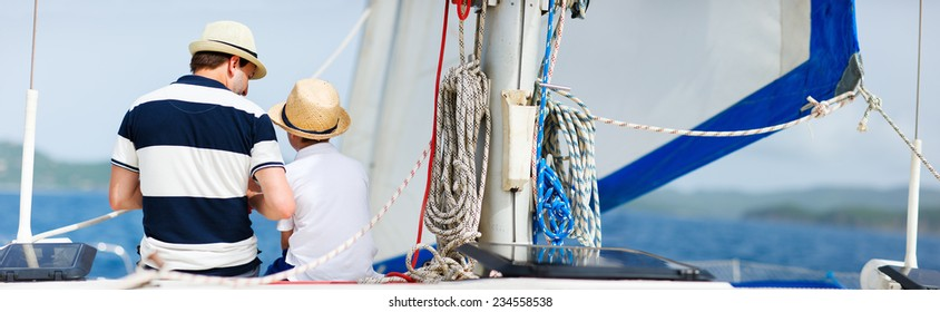 Back view of father and son family sailing on a luxury yacht or catamaran boat