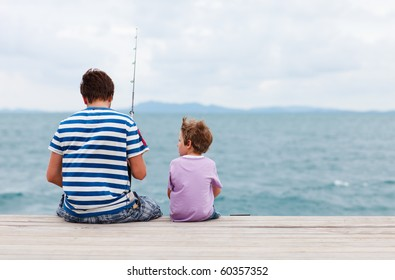 Back view of father and son fishing together from jetty
