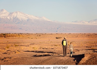 back view of father and son hiking together in atacama desert, chile, driest place on earth, with gorgeous mountain views, active family vacation concept