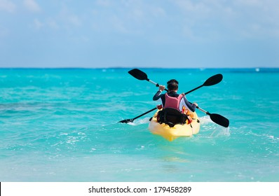 Back view of father and son kayaking at tropical ocean