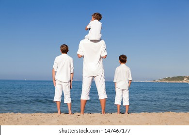 Back view of father and sons walking on beach, outdoor