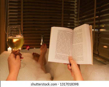 Back view of the feet of the young woman reading the book and drinking white wine in bath with foam and candles