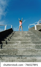 Back view of female athlete raising arms to the sky for celebrating fitness or running workout goals and success.