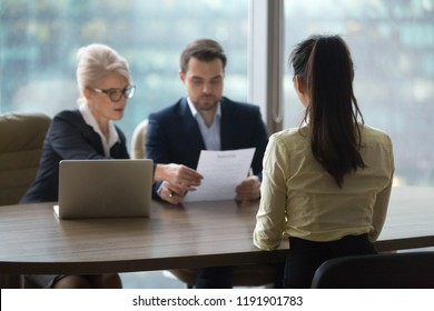 Back view of female candidate apply for position, interview in modern office, recruiters consider applicant candidature, reading resume, HR managers look through employee cv. Hiring concept