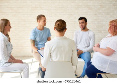 Back view of female coach working with group of young people sitting in circle during therapy session or training seminar in light spacious room