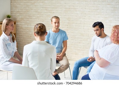 Back view of female coach working with group of young people sitting in circle during therapy session