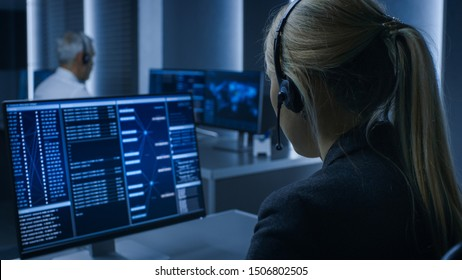 Back View of the Female Controller wearing Headset Working on Personal Computer, Monitoring Processes in the System Control Room full of Special Intelligence Agents.