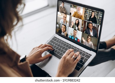 Back view of female employee communicate on video call with multiracial colleagues, woman worker conducts webcam group conference with business partners uses laptop and app