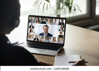 Back view of female employee engaged in team Webcam conference on laptop, have online briefing or consultation from home, woman worker speak talk on group video call with diverse colleagues