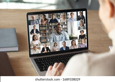 Back view of female employee speak talk on video call with diverse multiracial colleagues on online briefing, woman worker have Webcam group conference with coworkers on modern laptop at home